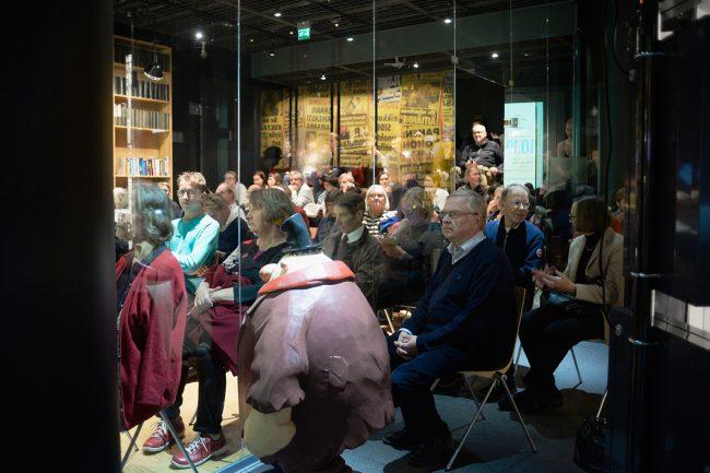 Kielestä kiinnostuneita kuulijoita museon auditoriossa ja sen ulkopuolella.
